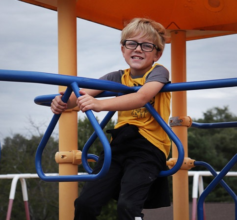 Young male student playing on playround equipment