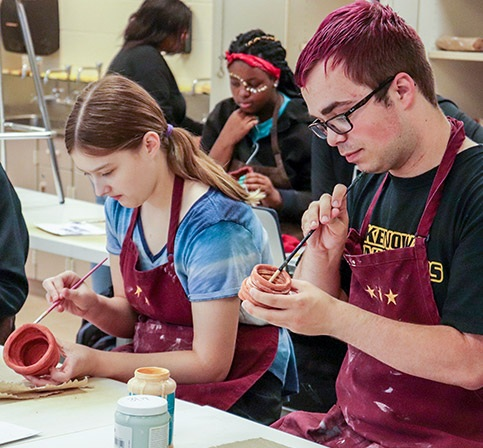 students work on pottery projects in art class