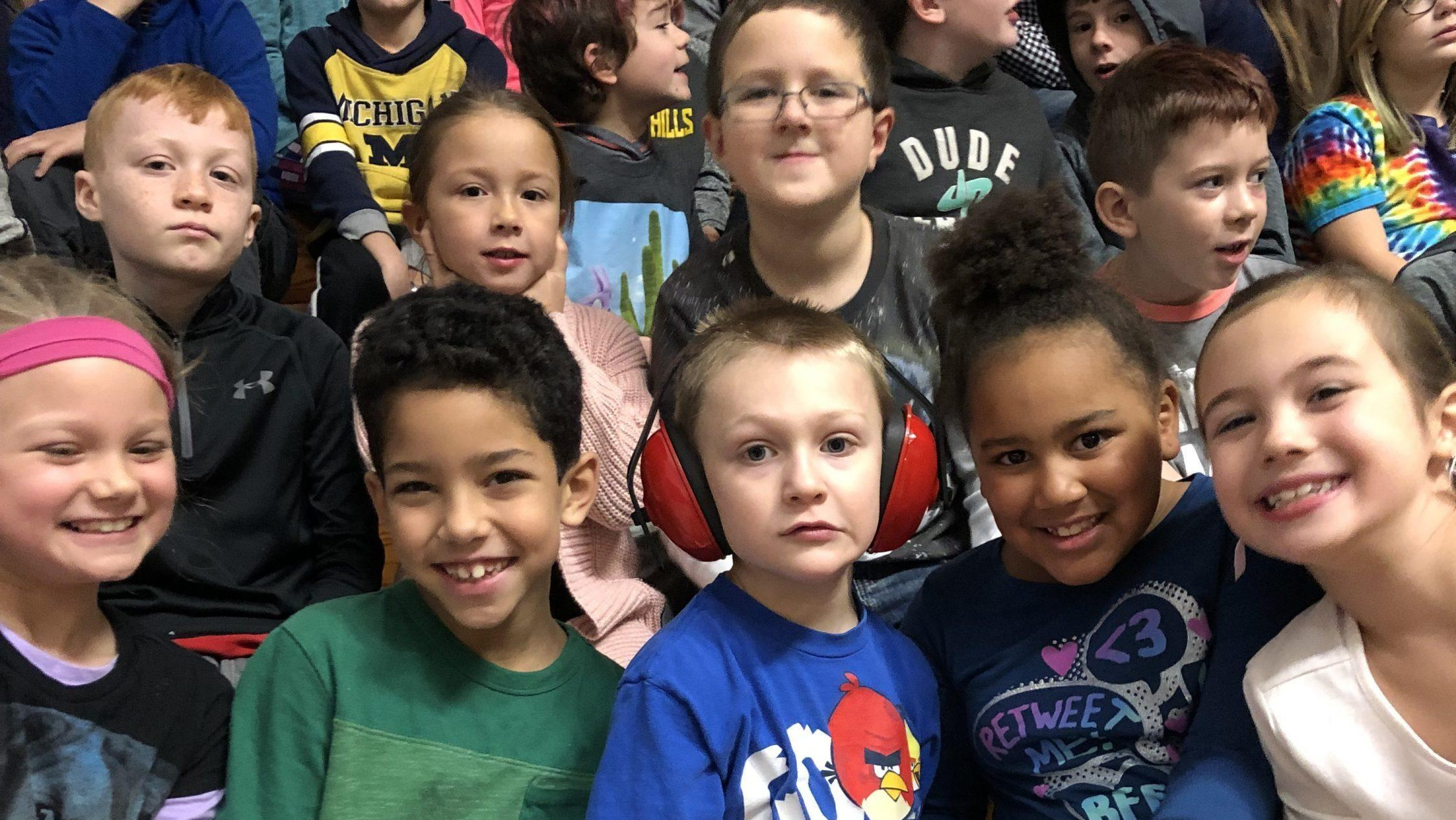 Jackson and his classmates in the bleachers at a school assembly.