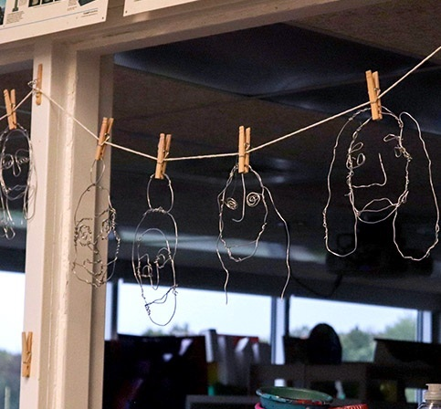 Portraits made of wire, hanging on a line with clothespins in a classroom